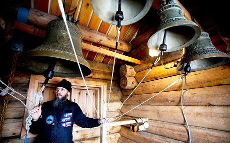 Priest Sophrony Kirilov pulls on the strings of the heavy Russian bells (Natacha Pisarenko/AP)